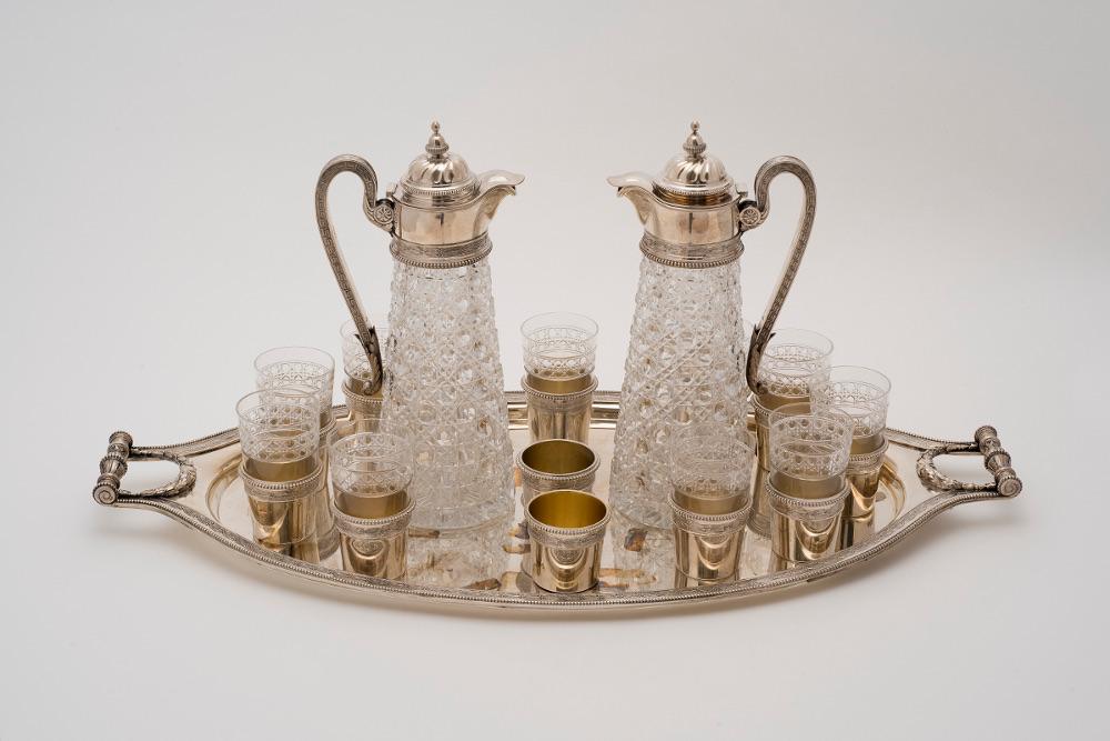 Сервиз для водки из двадцати пяти предметов: два кувшина, двенадцать серебряных оснований, десять хрустальных стопок, один поднос. 1895